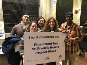 """Five people hold a sign that says """"I will volunteer at Pine Street Inn, St. Francis House, Project Place"""""""