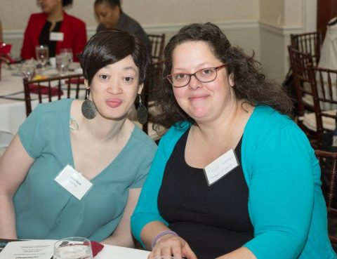 Two women pose at a table
