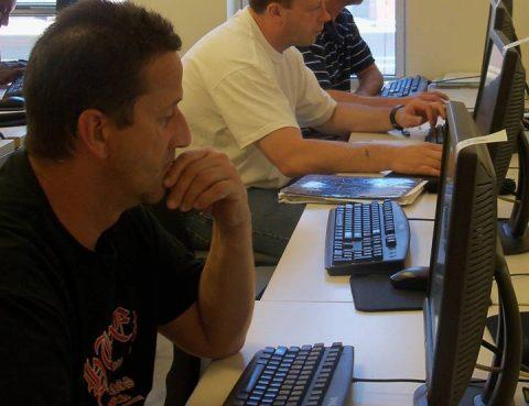 Three men using computers.