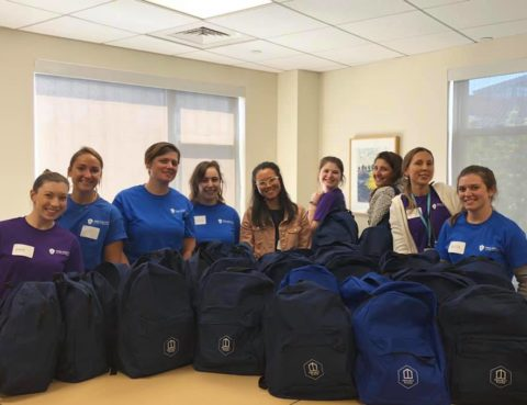 Mass General Hospital students posing in front of backpacks they filled with essential daily items to pass out to clients